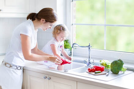 Mother and daughter washing vegetables in kitchen sink using clean, safe water that has been filtered in Orlando, FL